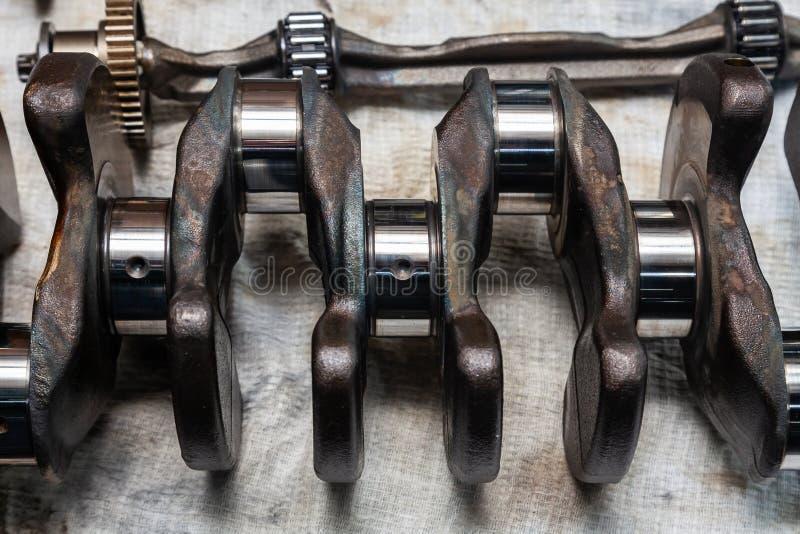为在一个工作凳的替换去除的汽车曲轴的特写镜头在车维修车间 汽车工业 库存照片