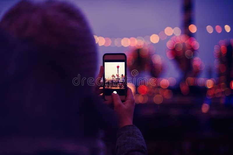 为在智能手机的妇女欧洲圣诞节市场场面照相 库存图片