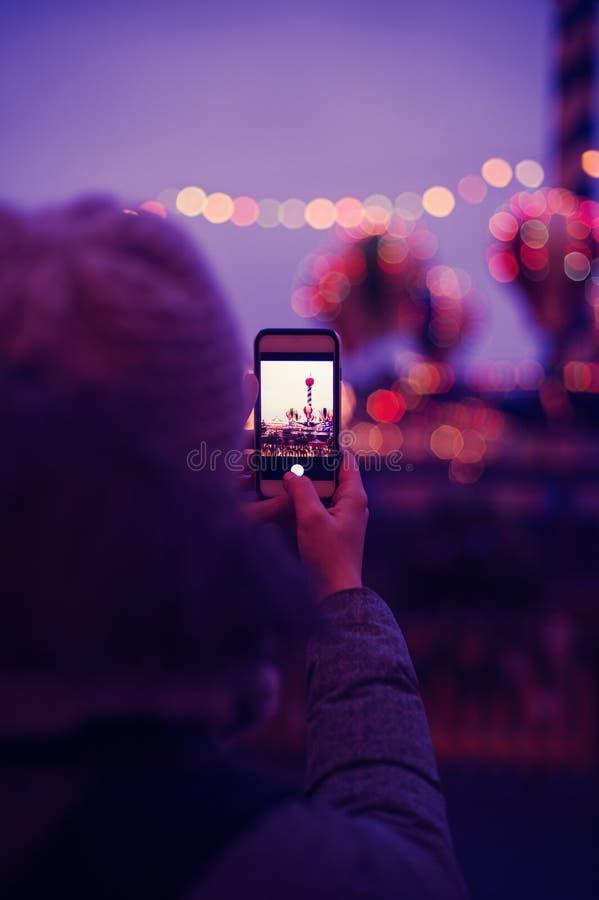 为在智能手机的妇女欧洲圣诞节市场场面照相 免版税库存照片