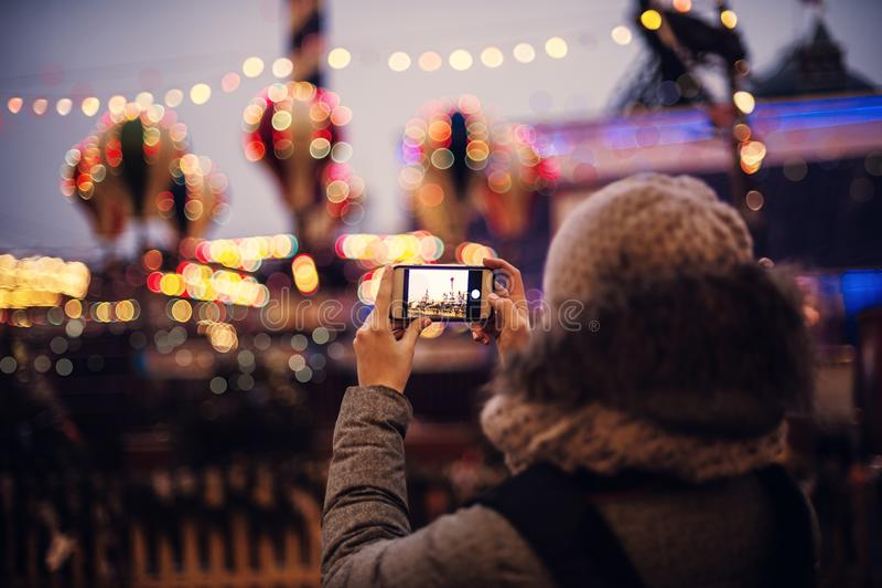 为在智能手机的妇女欧洲圣诞节市场场面照相 图库摄影