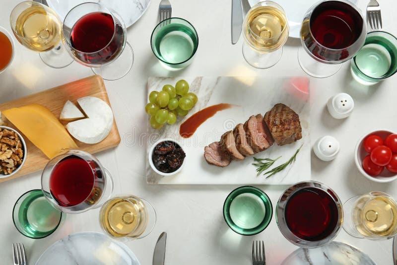 为在轻的桌上的晚餐和快餐供食的酒 库存照片