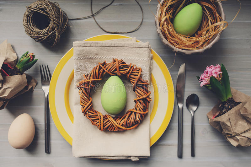 为复活节装饰的表用鸡蛋、风信花花和手工制造花圈 库存图片