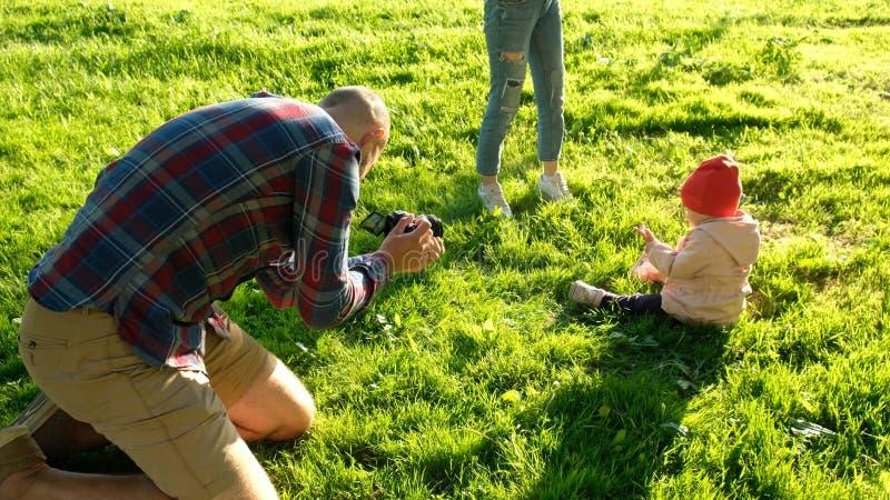 为女儿照相的年轻父亲在公园在日落 有愉快的家庭休息以自然的孩子 图库摄影