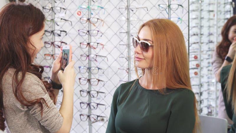 为她太阳镜的小女孩美好的妈妈购物照相 免版税库存照片