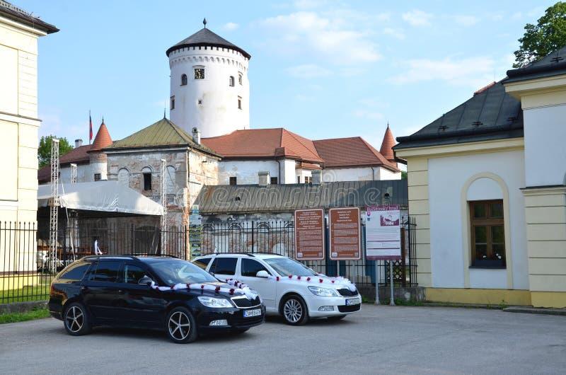 为婚姻的客人致力的两辆汽车装饰由在停车场的白色丝带在Budatin前面防御 免版税库存照片