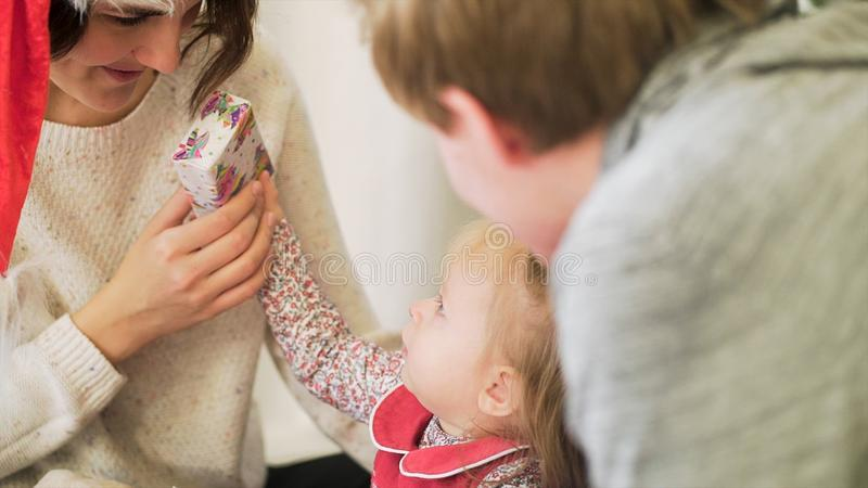 为幸福家庭,看他们逗人喜爱的孩子,快活的Christmass和新年概念的父母关闭  圣诞老人的母亲 免版税库存图片