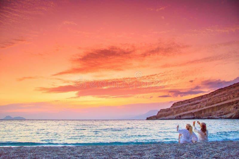 为惊人的日落照相的两名妇女在Matala,克利特海滩  图库摄影