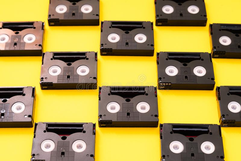 为摄制使用的葡萄酒微型DV盒式磁带在一天 样式由塑料视频拍摄制成在黄色背景 库存图片