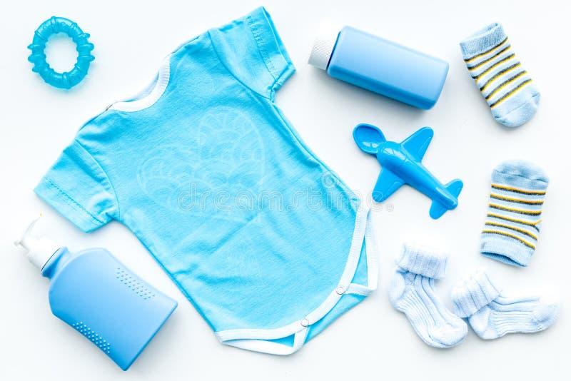 为新出生的男孩设置的蓝色 婴孩紧身衣裤、袜子、airplan玩具、肥皂和粉末在白色背景顶视图 库存照片