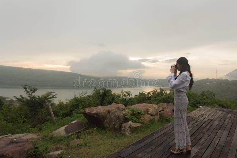 为日落照相的女性摄影师 免版税库存照片