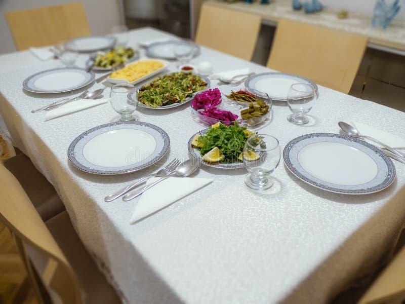 为晚餐准备的表布局在土耳其家庭房子里 在饭桌的板材、叉子匙子和沙拉盘 免版税图库摄影