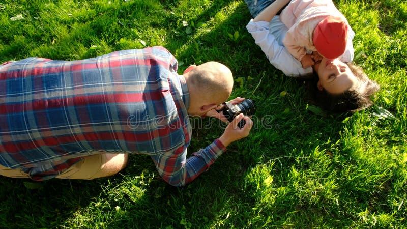 为母亲和女儿照相的年轻父亲使用在公园在日落 有愉快的家庭的一基于 库存照片