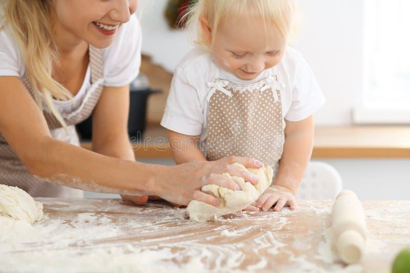 为母亲` s天照顾和她的烹调假日饼或曲奇饼的小女儿 愉快的家庭的概念在厨房里 库存照片