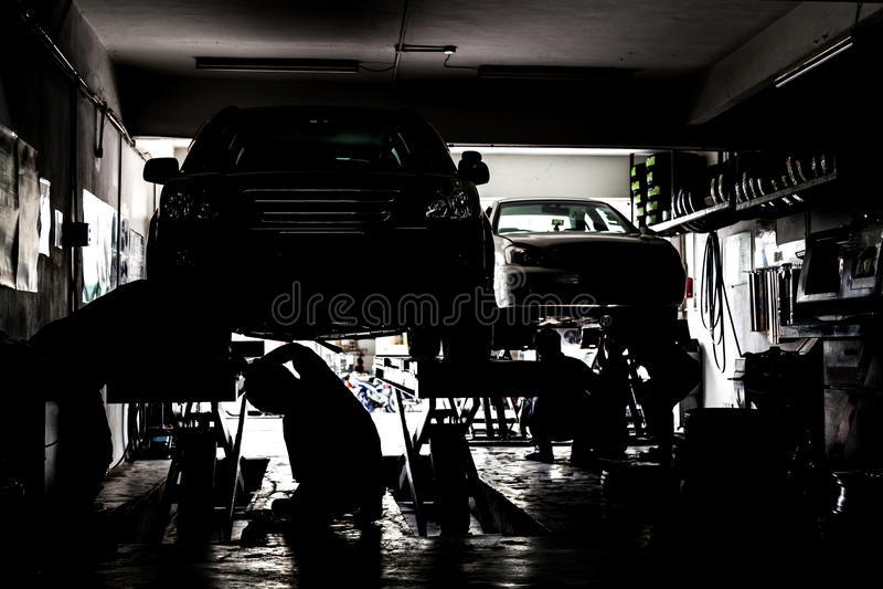 为汽车服务的机械工剪影在一个小型作坊 免版税库存照片
