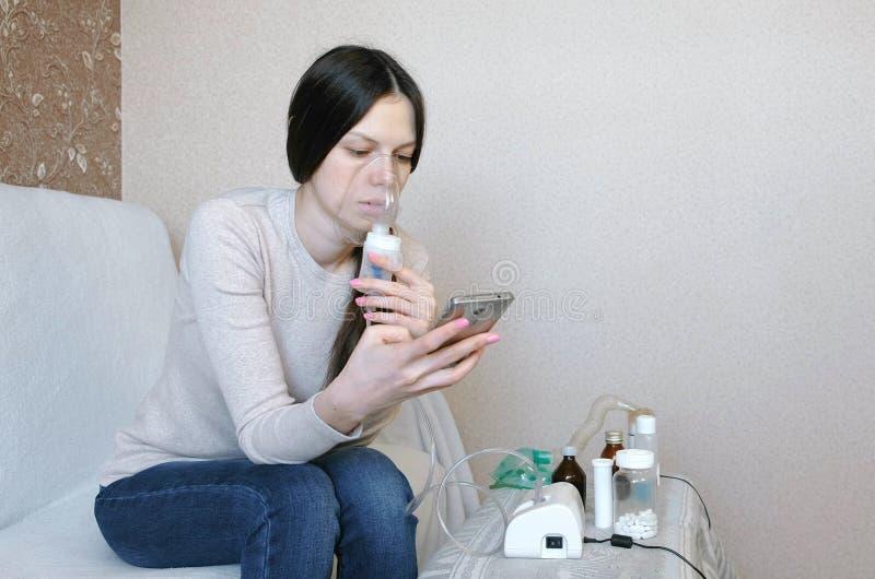 为治疗使用雾化器和吸入器 吸入通过吸入器面具和看电话的少妇 侧视图 库存图片