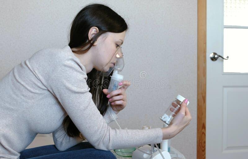 为治疗使用雾化器和吸入器 吸入通过吸入器面具的少妇看一个小瓶药片 端 免版税库存照片