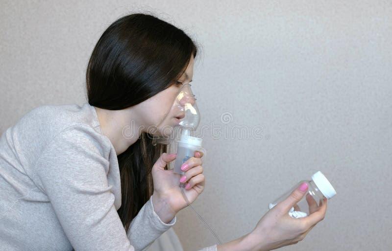 为治疗使用雾化器和吸入器 吸入通过吸入器面具的少妇看一个小瓶药片 端 库存图片