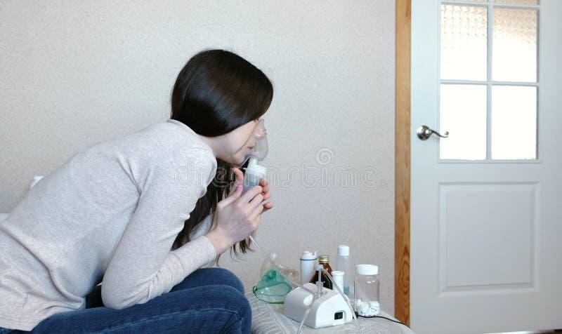 为治疗使用雾化器和吸入器 吸入通过吸入器面具的少妇 侧视图 免版税库存照片
