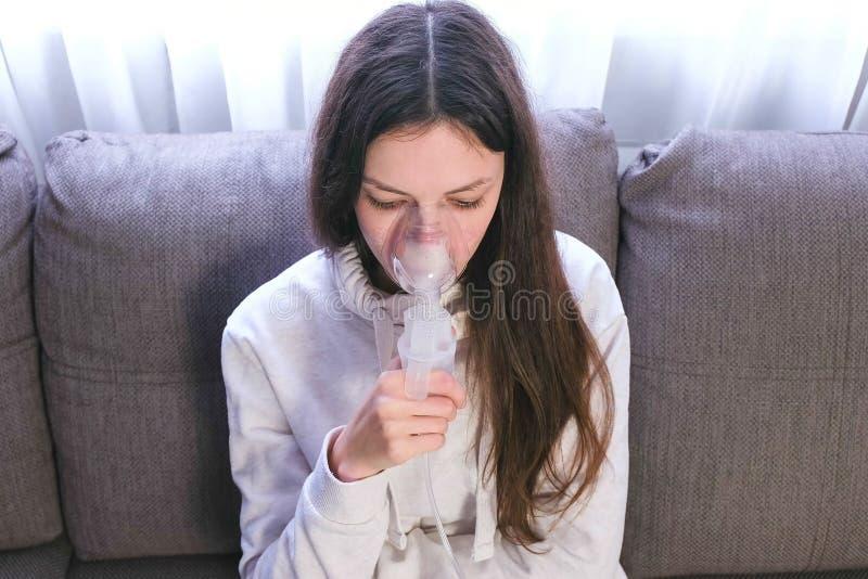 为治疗使用雾化器和吸入器 吸入通过吸入器面具的年轻女人坐沙发 免版税图库摄影