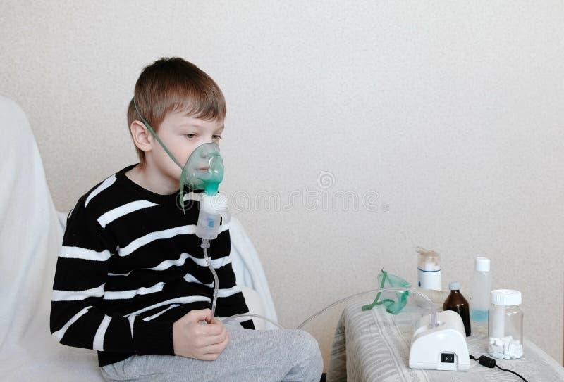 为治疗使用雾化器和吸入器 吸入通过吸入器面具的男孩 侧视图 库存图片