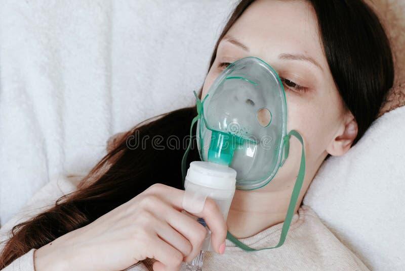 为治疗使用雾化器和吸入器 少妇吸入通过吸入器面具的` s面孔说谎在长沙发 端 免版税库存照片