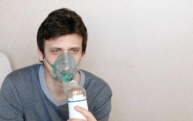 为治疗使用雾化器和吸入器 特写镜头年轻人吸入通过吸入器面具的` s面孔 正面图 免版税图库摄影