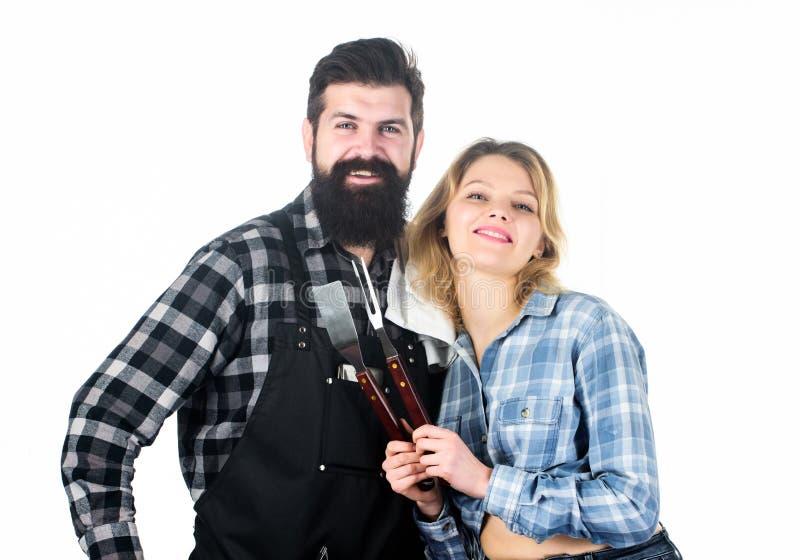 为烤肉的工具户外 野餐和烤肉 烹饪概念 人有胡子的行家和女孩准备好烤肉 库存图片