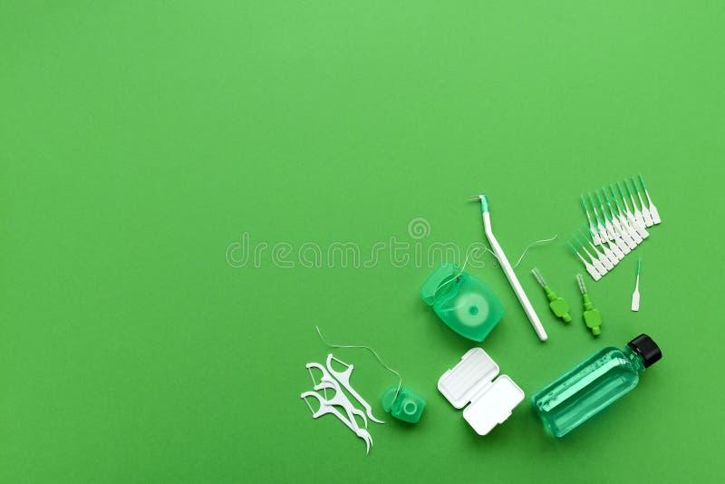 为牙齿保护的不同的工具在绿色背景 牙刷、清洁剂、绣花丝绒、flossers、蜡括号的和牙齿之间刷子 免版税库存图片