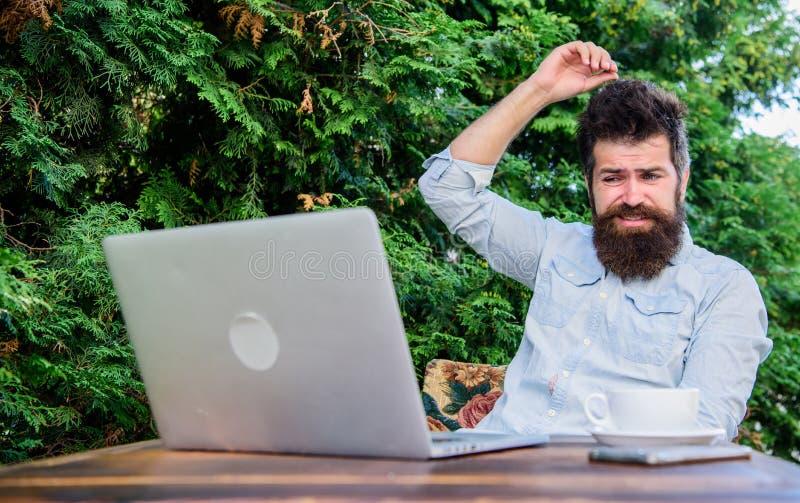 为网上杂志写文章 有胡子的行家膝上型计算机冲浪的互联网 寻找启发的人 记者 免版税库存图片