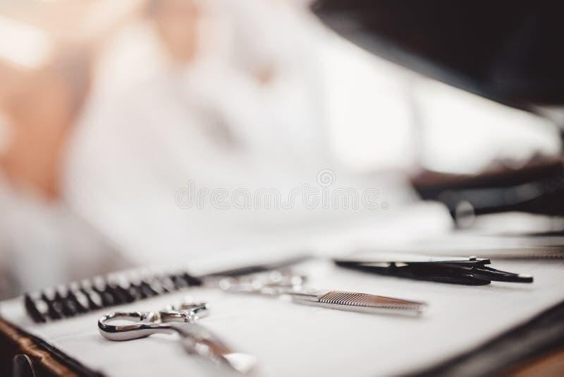 为美发师的工具:剪刀,梳子在前景,客户坐在椅子背景中 库存照片