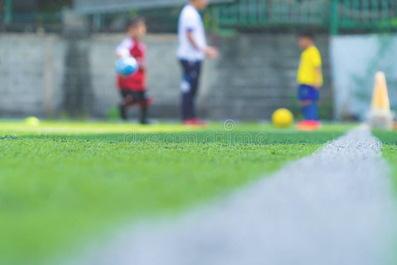 为背景弄脏的儿童训练的足球学院 免版税库存照片