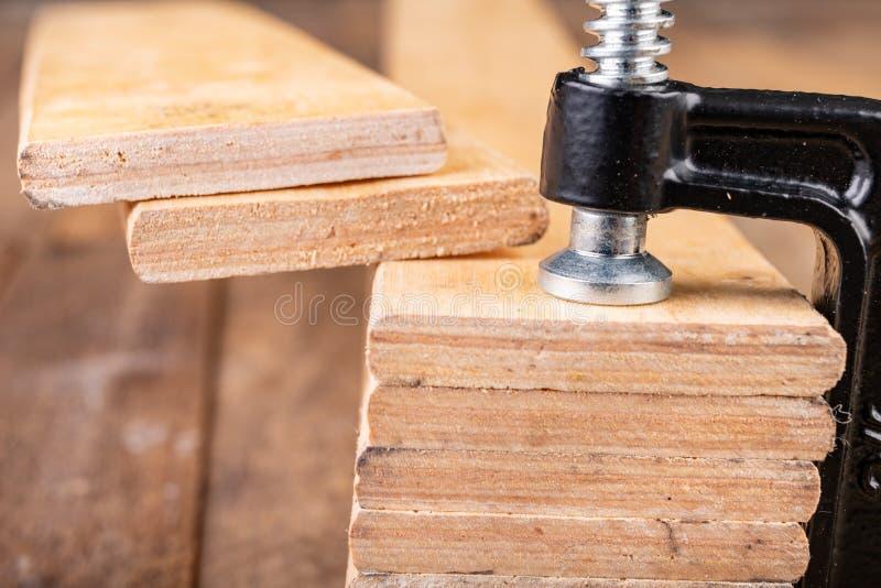 为胶合板条使用的小细木工技术钳位 木匠的辅助部件在车间桌上 库存图片