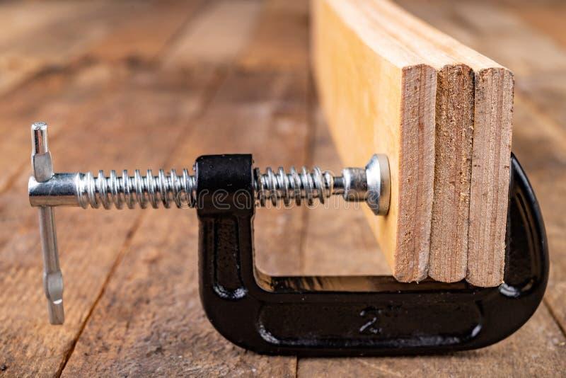 为胶合板条使用的小细木工技术钳位 木匠的辅助部件在车间桌上 免版税库存图片