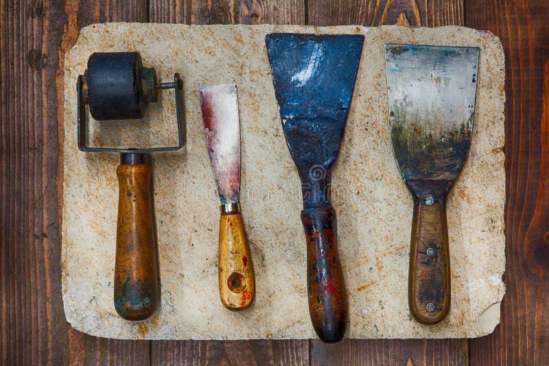 为艺术家车间的减速火箭的设计工具:橡胶路辗、不同的大小油灰刀在石板材和木背景 库存图片