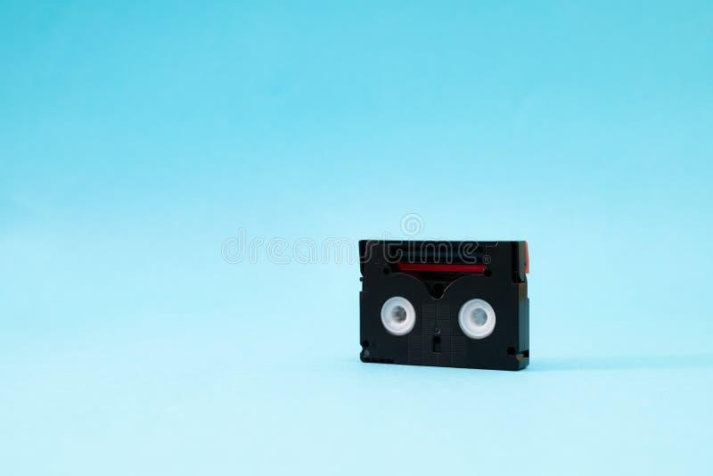 为记录录影使用的葡萄酒微型DV盒式磁带在一天 在蓝色背景的塑料,磁性,模式影片磁带 免版税图库摄影