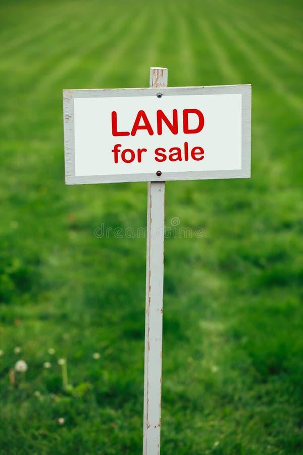 为销售标志登陆反对被整理的草坪背景 库存图片