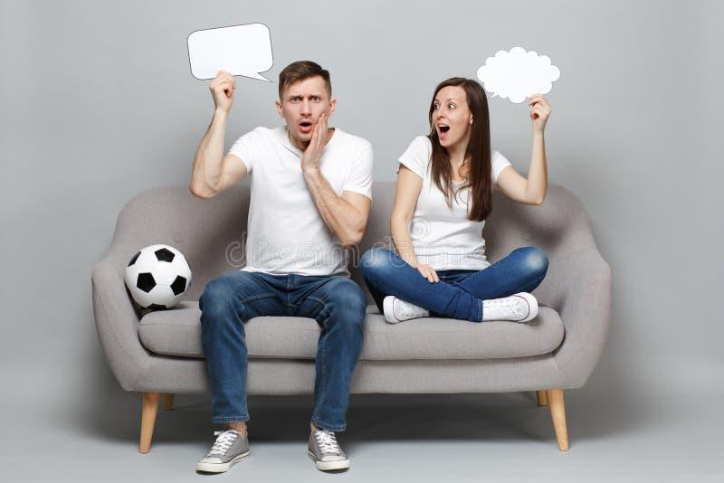 为难的夫妇妇女人足球迷欢呼与足球的喜爱的队拿着空的空白的发言权云彩的支持 免版税图库摄影