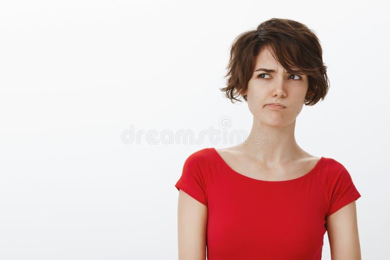 为难的缺乏信心的体贴的逗人喜爱的俏丽的考虑困难的选择傻笑的皱眉的妇女短的理发查找斜眼看 库存图片