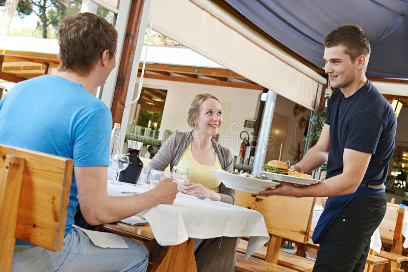 为青年人服务的侍者在餐馆 免版税库存图片