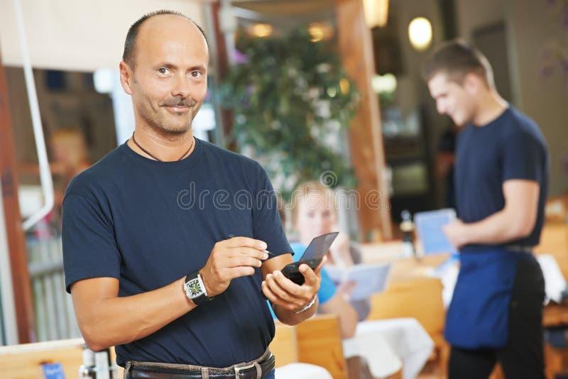 为青年人服务的侍者在餐馆 图库摄影