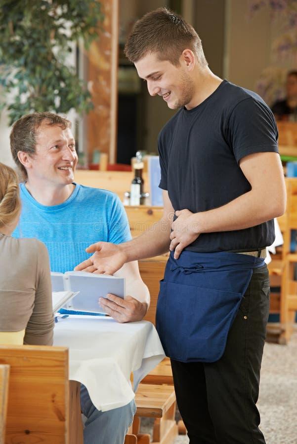 为青年人服务的侍者在餐馆 库存照片