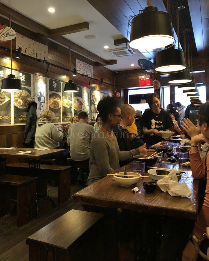 为顾客服务的女服务员在日本面店纽约食物吃趋向 库存照片
