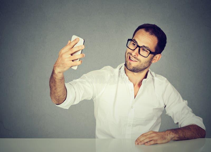 为他照相的年轻滑稽的看的人与巧妙的电话的自已 免版税库存照片