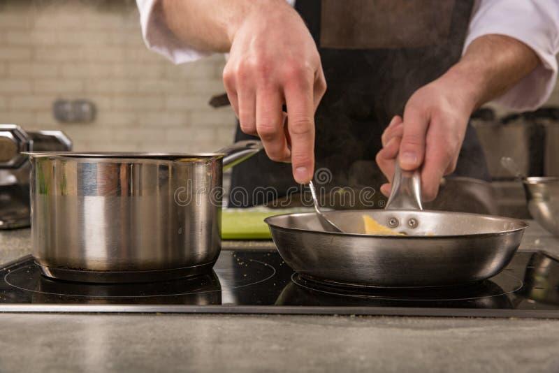 主厨在火炉的餐馆厨房里与平底锅 库存照片