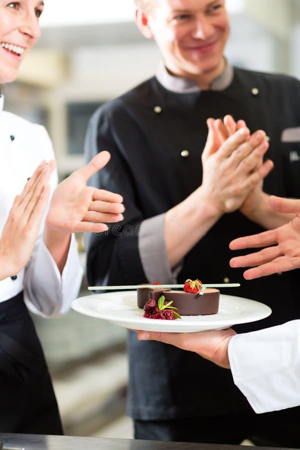主厨小组在餐馆厨房里用点心 免版税库存照片