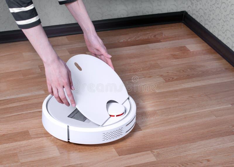 主妇打开白色机器人吸尘器上层覆盖取消机器人擦净人收集的垃圾 简化您的家 免版税库存图片