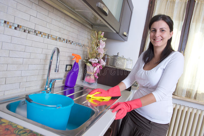 主妇清洁家具在厨房里 免版税图库摄影