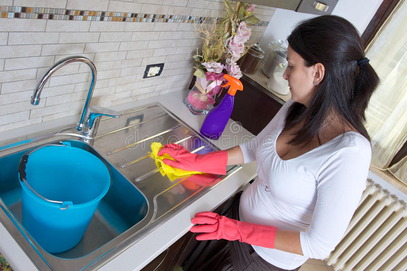 主妇清洁家具在厨房里 免版税库存照片