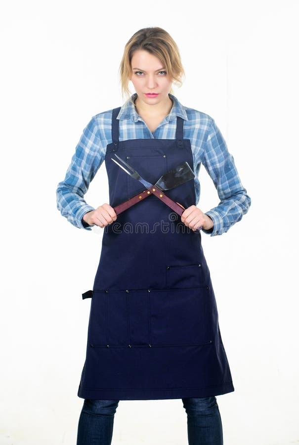 主妇疲倦了 厨师围裙的俏丽的女孩 妇女举行厨房用具 为厨师的工具 烹调食谱的食物 野餐 库存照片