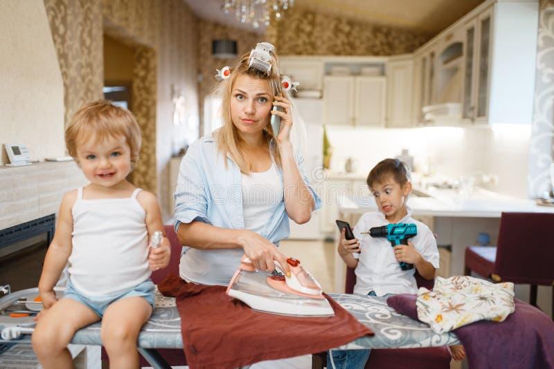 主妇谈话由电话,无所事事的孩子  免版税图库摄影
